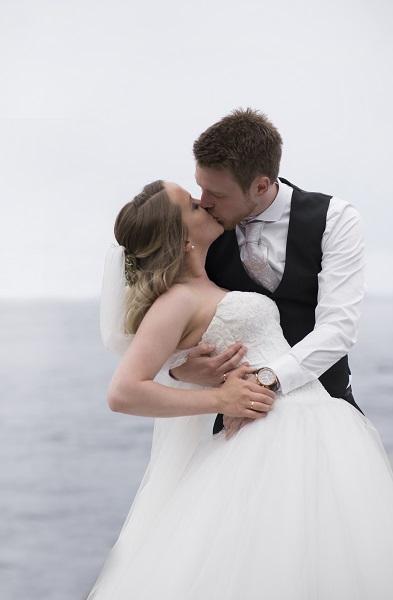 brudepar kysser ved sjøen
