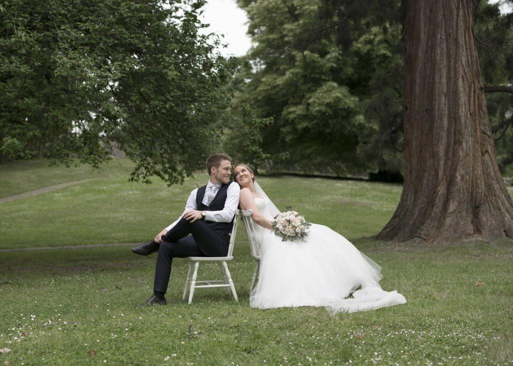 Brudepar sitte under treet på hvite stoler