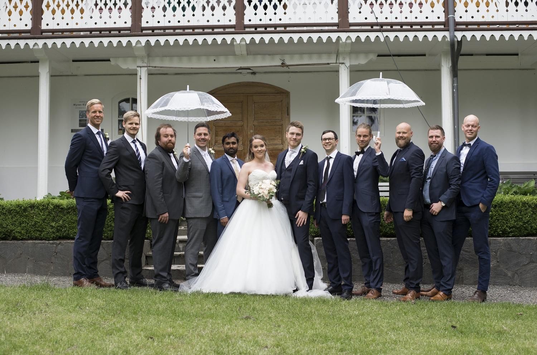 bryllup gruppe portrett med paraplyer